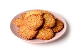 Lokalisiertes Bündel runde Kekse mit indischem Sesam auf einem hellrosa Winkel des Leistungshebels lizenzfreies stockbild