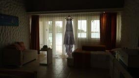 Lokalisiertes Brauthochzeitskleid im Bungalowraum mit blauer Lagune auf Hintergrund, Kamera auf Schieber Szenisches hinteres des  stock video
