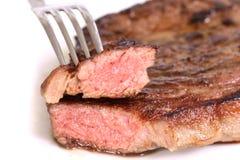 Lokalisiertes gedientes Stück des Mediums grillte Rindfleischsteak auf weißem Hintergrund Lizenzfreie Stockbilder