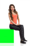 Lokalisiertes Mädchen, das auf grüne Farbenreinheits-Schlüsselkasten sitzt Stockfotos