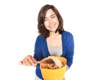 Lokalisiertes Porträt der jungen glücklichen Frau, die Teigwaren auf Weiß zubereitet Stockfotografie