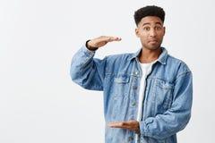 Lokalisiertes Porträt des jungen lustigen dunkelhäutigen Mannes mit Afrofrisur im zufälligen weißen Hemd unter Denimjacke lizenzfreie stockfotografie