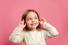 Lokalisiertes Porträt des schönen kleinen Mädchens mit den gekreuzten Fingern, die oben schauen und Wunsch machen Stockbilder
