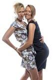 Lokalisiertes Porträt von scherzenden Schwestern auf Weiß Lizenzfreie Stockfotos