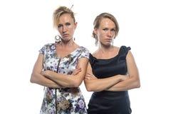 Lokalisiertes Porträt von zwei ernsten Schwestern auf Weiß Lizenzfreies Stockfoto