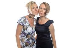 Lokalisiertes Porträt von zwei scherzenden Schwestern auf Weiß Stockfoto