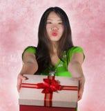 Lokalisiertes rosa Hintergrundporträt der jungen glücklichen und schönen asiatischen Chinesin, welche die Geschenkbox gibt oder e lizenzfreies stockfoto