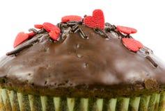 Lokalisiertes Schokoladenmuffin mit roten Zuckerherzen Stockbilder