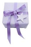 Lokalisiertes violettes Weihnachtsgeschenk eingewickelt im Papier mit einem Stern Lizenzfreies Stockbild