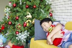 Lokalisierung auf Weiß Netter kleiner Junge, der ein Geschenk beim Schlafen umarmt stockfoto