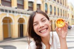 LokalMacao mat - kvinnavisning pastellfärgade de nata arkivbild