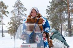 Lokalna kobieta w krajowym kostiumu jedzie snowmobile obrazy royalty free