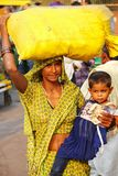 Lokalna kobieta z małej dziewczynki przewożenia torbą na jej głowie przy Kinari Zdjęcia Royalty Free