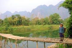 Lokalna kobieta z tradycyjnym odziewa przy drewnianym mostem w Vang Vieng, Laos Zdjęcie Royalty Free