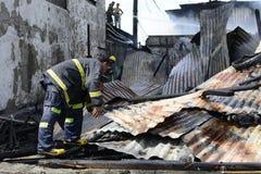 Lokalna palacz pomoc gasi ogienia podczas domu ogienia który patroszył wewnętrznych szanta domy fotografia stock
