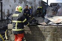 Lokalna palacz pomoc gasi ogienia podczas domu ogienia który patroszył wewnętrznych szanta domy obrazy stock