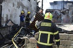 Lokalna palacz pomoc gasi ogienia podczas domu ogienia który patroszył wewnętrznych szanta domy obraz royalty free