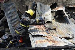 Lokalna palacz pomoc gasi ogienia podczas domu ogienia który patroszył wewnętrznych szanta domy zdjęcie royalty free