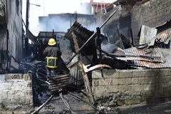 Lokalna palacz pomoc gasi ogienia podczas domu ogienia który patroszył wewnętrznych szanta domy obrazy royalty free