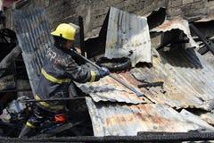 Lokalna palacz pomoc gasi ogienia podczas domu ogienia który patroszył wewnętrznych szanta domy zdjęcie stock