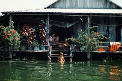lokalna rodzina cieszy się spokojnego popołudnie przy ich stilt domu domem podczas gdy goljący skąpanie i mieć obraz stock