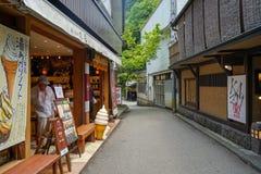 Lokalnego rocznika uliczna atmosfera z niezidentyfikowanym mężczyzna w lodów sklepowych i restauracyjnych budynkach, Kurokawa Ons fotografia royalty free
