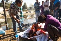 Lokalni ludzie podczas kremaci ceremonii wzdłuż świętej Bagmati rzeki w Bhasmeshvar Ghat przy Pashupatinath świątynią w Kathmandu zdjęcia stock