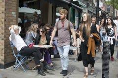 Lokalni ludzie siedzą przy stołem w ulicznych kawiarniach podczas rynku na Broadway drodze Pstrobarwny tłum wędruje past Fotografia Royalty Free