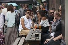 Lokalni ludzie siedzą przy stołem w ulicznych kawiarniach podczas rynku na Broadway drodze Pstrobarwny tłum wędruje past Zdjęcie Royalty Free