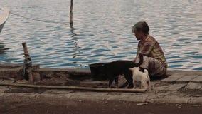Lokalny kobiety obsiadanie na brzeg z psami w Trunyan wiosce, artykuł wstępny zbiory wideo