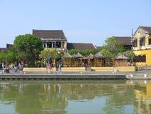 Lokalt folk, fartyg, gulinghus vid floden och turister i Hoi An den forntida staden royaltyfria bilder
