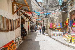 Lokalt folk på en gata i stenstad Stenstaden är den gamla delen av den Zanzibar staden, huvudstaden av Zanzibar, Tanzania Arkivbild