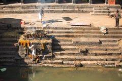 Lokalt folk under kremeringceremonin längs den heliga Bagmati floden i Bhasmeshvar Ghat på den Pashupatinath templet i Katmandu Arkivfoton