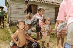 Lokalt kubanska byfolk och ungar som rymmer en torkduk och gods Arkivfoton