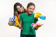 Lokalvård, inhemska arbetsuppgifter och teamworkbegrepp Två tonårs- systrar som bär gula skyddande handskar, och innehav dem för  Royaltyfri Foto