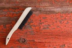 Lokalvårdborste mot röd träbakgrund royaltyfri fotografi