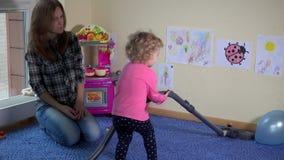 Lokalvårdrum för ung kvinna och barnmed dammsugare lager videofilmer