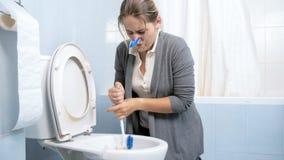 Lokalvårdtoaletten för den unga kvinnan och att försöka att få befriar av dålig lukt royaltyfri fotografi