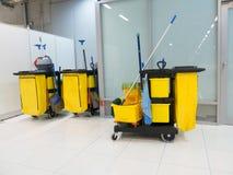 Lokalvårdvagn i stationen Rengörande hjälpmedel cart, och gulinggolvmopphinken väntar på lokalvård Hink och uppsättning av lokalv Arkivfoton