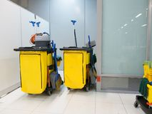 Lokalvårdvagn i stationen Rengörande hjälpmedel cart, och gulinggolvmopphinken väntar på lokalvård Hink och uppsättning av lokalv Arkivfoto