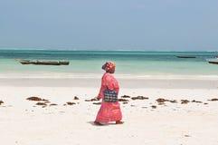 LokalZanzibar kvinna i ljus ämbetsdräkt på stranden nära indiern Fotografering för Bildbyråer