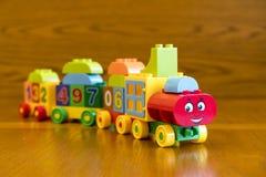 Lokomotiv för barn` s med vagnar, på en träbakgrund Fotografering för Bildbyråer