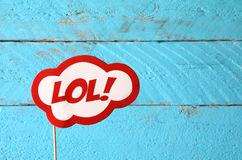 LOL bubble text comic retro sign. In front of wooden background stock photography