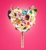 Lolipop dulce en forma del corazón de crema azotada con los dulces, jaleas, vista delantera del corazón Tendencia loca de la comi imagenes de archivo