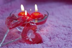 Lolipops and candles in the form of hearts on a pink background. Romantic concept of Valentines Day. Tinted photo. Stock Image