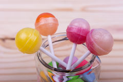 Lolipops in jar on wooden table Stock Photography