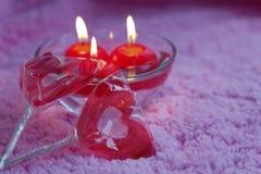 Lolipops und Kerzen in Form von Herzen auf einem rosa Hintergrund Romantisches Konzept des Valentinsgruß-Tages Abgetöntes Foto Stockbild