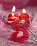 Lolipops und Kerzen in Form von Herzen auf einem rosa Hintergrund Romantisches Konzept des Valentinsgruß-Tages Abgetöntes Foto Lizenzfreies Stockbild