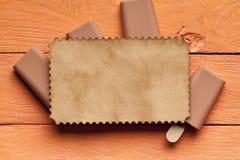 Lollies и чистый лист бумаги льда покрывают на деревянной предпосылке Стоковое Изображение RF