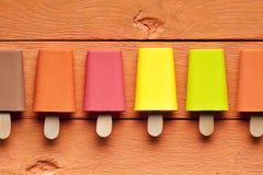 Lollies de gelo coloridos em pranchas de madeira imagens de stock